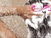 Mulher lavando os cabelos com shampoo