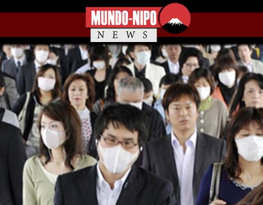 Japoneses caminhando pelas ruas usando máscara