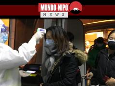 Autoridades de saúde em roupas de proteção verificam a temperatura corporal dos passageiros que chegam da cidade de Wuhan