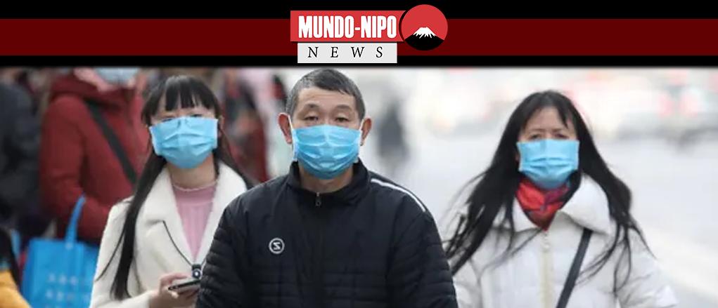 Os residentes chineses usam máscaras enquanto aguardam em uma rodoviária perto do mercado atacadista