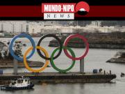 Uma barcaça carregando os anéis olímpicos é vista perto da ponte do arco-íris, no distrito de Odaiba, em Tóquio, na sexta-feira.