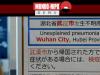 Uma mulher usando uma máscara passa por um aviso de quarentena sobre o surto de coronavírus em Wuhan