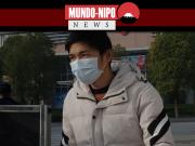 homem caminhando em frente a um hospital