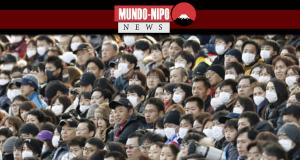 Os fãs usam máscaras durante a Supercup de sábado no Estádio Saitama.