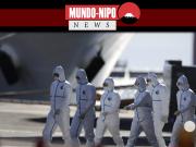 Trabalhadores médicos com suítes protetoras se afastam do navio de cruzeiro Diamond Princess