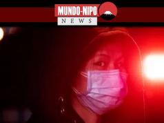 Uma mulher chinesa usa uma máscara próximo a uma viatua de policia de Pequim