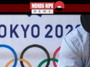 Homem sentado em frente a um anuncio dos jogos olimpicos de 2020