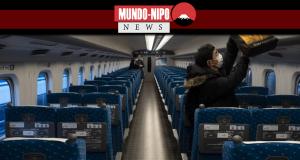 um passageiro poe sua bagagem no bagageiro de um trem-bala que ia para Kyoto